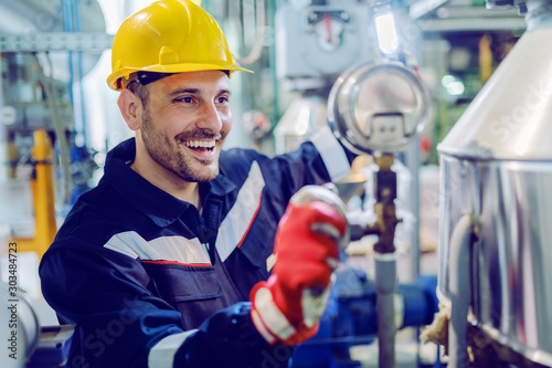 Hardworking smiling blue collar worker in protective working suit and with helmet adjusting temperature on boiler while standing in factory and holding lamp Canvas-taulu