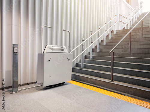 Fototapeta Wheelchair lift with stairs Disability elevator Indoor Public building Universal design facility obraz
