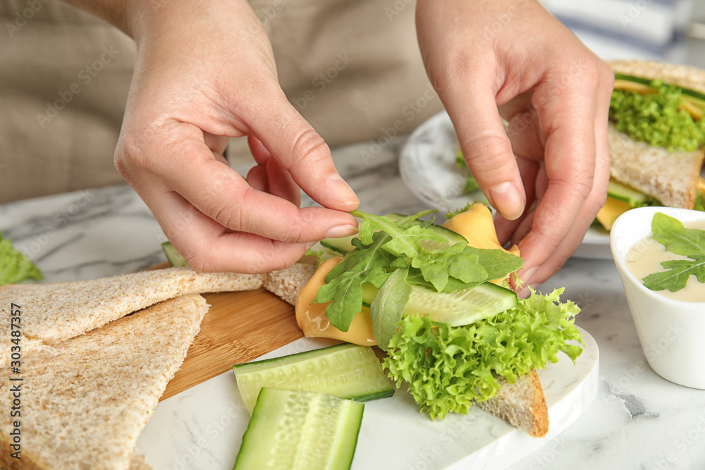 Fototapety, obrazy: Woman making tasty sandwich at white marble table, closeup