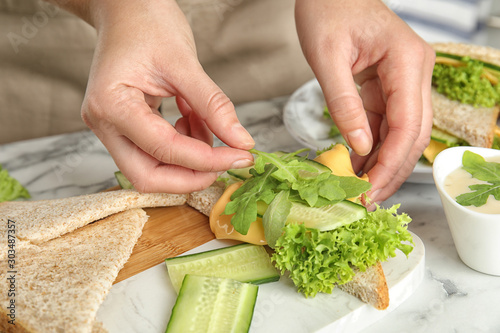 Woman making tasty sandwich at white marble table, closeup