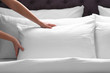 Woman fluffing white pillow on bed, closeup