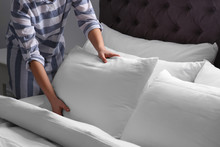 Woman Fluffing White Pillow On...