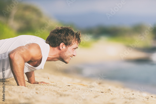 Fit man training on beach doing push-ups workout summer fitness lifestyle.
