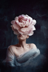 Strange fine art concept. The body of a woman, her head is a peony