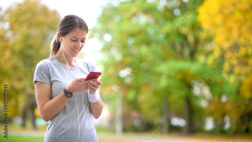 Girl athlete jogging in the evening park. Resting holds a smartphone and listens to music. Workout. Healthy lifestyle.