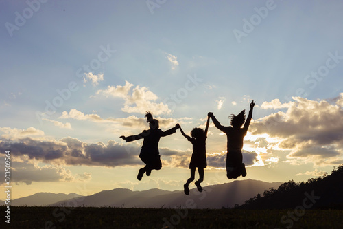 Silhouette group people jumping playing on mountain at sunset time.