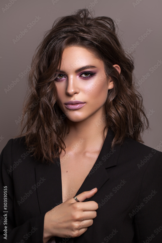 Fototapeta Portrait of young beautiful brunette model with violet professional make up, trendy wavy hairdo and perfect skin.
