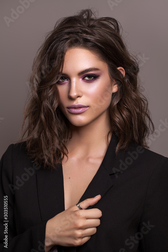 Photo Portrait of young beautiful brunette model with violet professional make up, trendy wavy hairdo and perfect skin