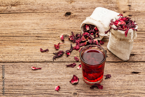Garden Poster Tea Hot hibiscus tea. Dry petals, linen sacks. Healthy food and self-care concept. Old wooden boards backgrounds