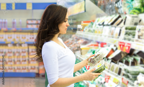 Obraz na plátně Woman choosing daily products at supermarket