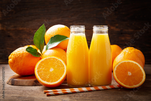 Poster Sap bottles of fresh orange juice with fresh fruits