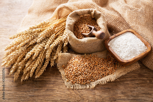 Fototapeta wheat ears, grains and bowl of flour on a wooden table obraz