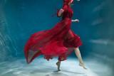 Female figure in a dark red dress underwater.