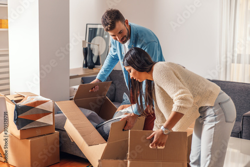 Fototapeta Smiling young couple move into a new home carrying boxes of belongings. obraz