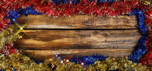 Christmas frame tinsel decorations with copy space from wooden boards. Top view horizontal long frame.