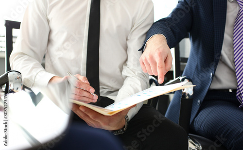 Obraz Male hand in suit and tie showing something important in tax interview document - fototapety do salonu
