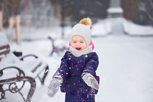 Cute Baby Girl Playing Outdoor In Winter Fresh White Snow Outdoor. Child Snowing Fresh Snow Up In Air Cheerfully. Horizontal Color Photography.