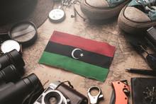 Libya Flag Between Traveler's Accessories On Old Vintage Map. Tourist Destination Concept.