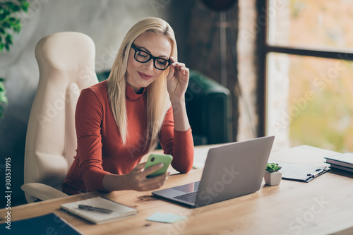 Charming woman chief boss wearing orange turtleneck sit table get social media notification read sms from clients in office wear red turtneck