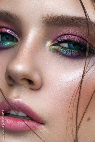 Photographie A very close up photo of young model with blue eyes, rainbow eyeshadows and perfect skin