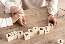 Cropped View Of Retired Couple Sitting Near Wooden Cubes With Alzheimer Letters