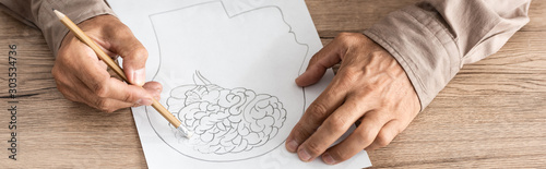 panoramic shot of retired man with alzheimer disease drawing human head and brai Canvas Print