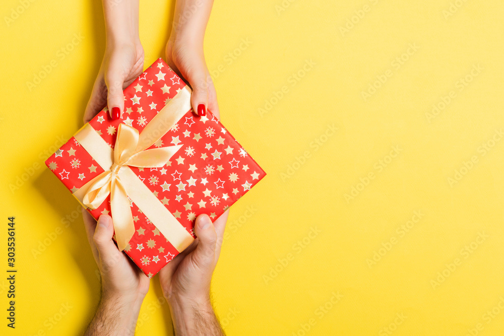 Fototapety, obrazy: Top view of a man and a woman giving and receiving gift for a holiday on colorful background. Love and relationship concept with copy space