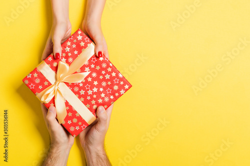 Obraz Top view of a man and a woman giving and receiving gift for a holiday on colorful background. Love and relationship concept with copy space - fototapety do salonu