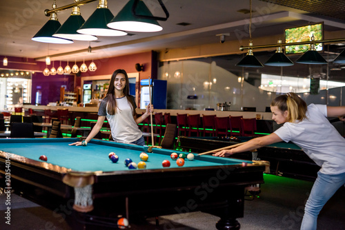 Fotografie, Obraz Smiling friends with cues playing billiard in pub