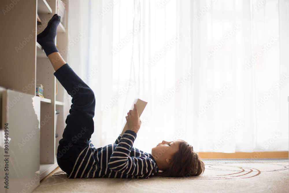 Fototapeta Cute child, boy, reading a book at home