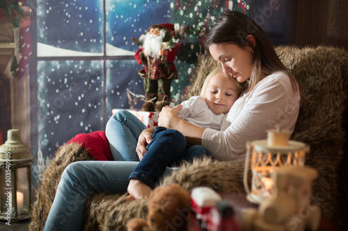 Obraz Beautiful young mother, hugging her toddler boy, sitting in cozy chair on Christmas - fototapety do salonu