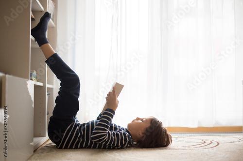 Obraz Cute child, boy, reading a book at home - fototapety do salonu
