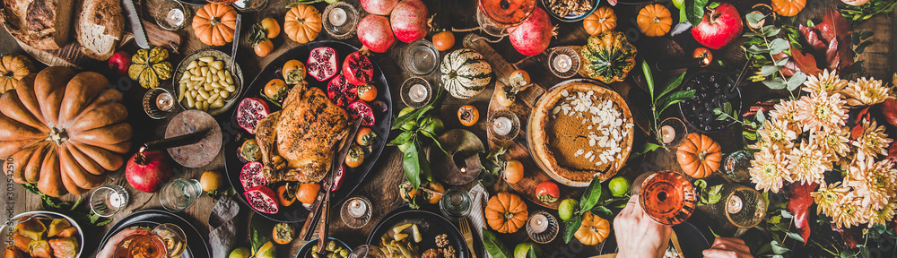 Fototapety, obrazy: Family celebrating Thanksgiving day. Flat-lay of peoples hands with glasses of rose wine over Friendsgiving table with Autumn food, roasted turkey and pumpkin pie over wooden table, wide composition