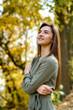 Female portrait. Brunette woman portrait in autumn park wearing olive dress