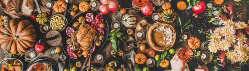 Family celebrating Thanksgiving day. Flat-lay of peoples hands with glasses of rose wine over Friendsgiving table with Autumn food, roasted turkey and pumpkin pie over wooden table, wide composition