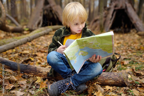 Little boy scout is orienteering in forest. Child is sitting on fallen tree and looking on map on background of teepee hut.