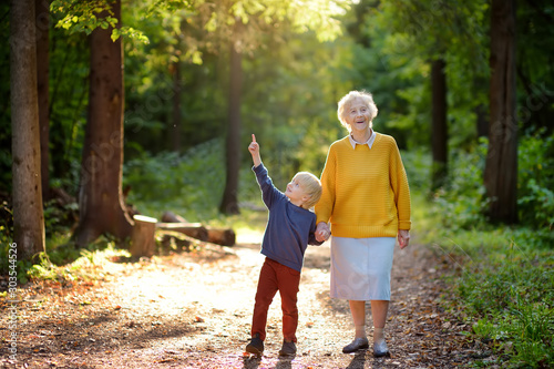 Fototapeta Elderly grandmother and her little grandchild walking together in sunny summer park