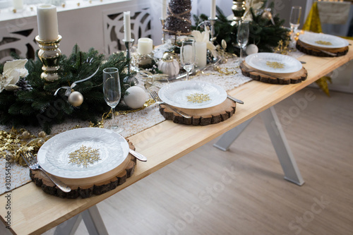 Obraz New year table decor. Christmas table with candles, plates and decorations. - fototapety do salonu