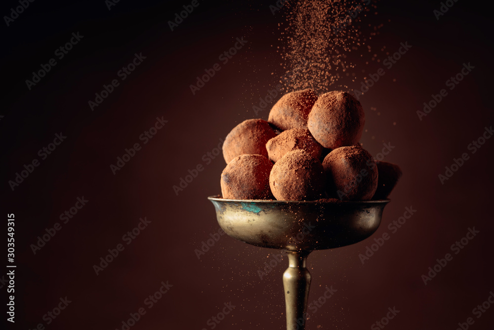 Fototapety, obrazy: Chocolate truffles in old brass vase sprinkled with cocoa powder.