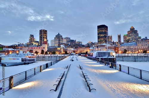 Obraz Snow-covered benches, pier, waterfront walkway, harbor, and downtown Montreal after sunset in winter - Montreal, Canada - fototapety do salonu
