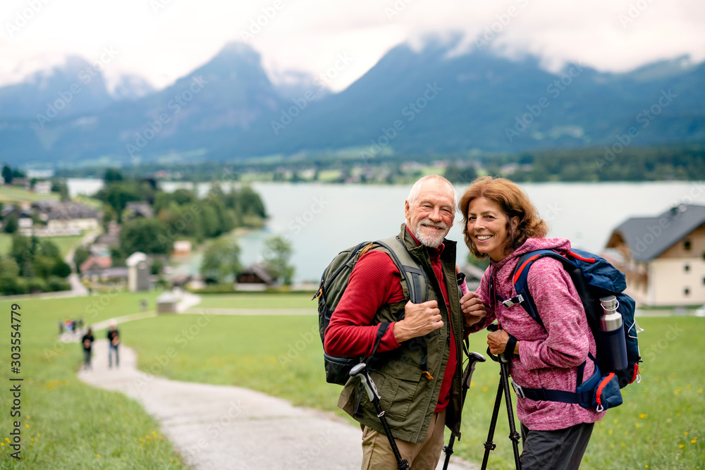 Fototapety, obrazy: Senior pensioner couple with nordic walking poles hiking in nature.