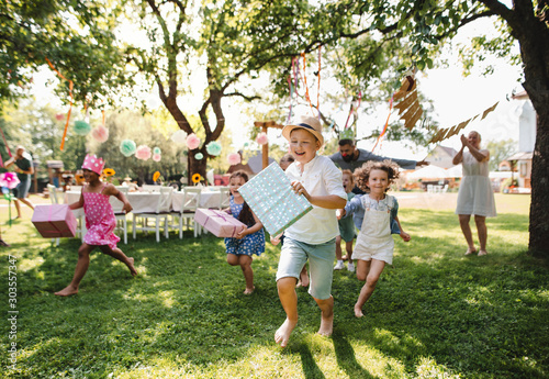 Obraz Small children ruunning with present outdoors in garden on birthday party. - fototapety do salonu