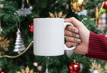 Women Hand Holding White Ceramic Coffee Cup On Christmas Tree Background. Mockup For Creative Advertising Text Message Or Promotional Content.