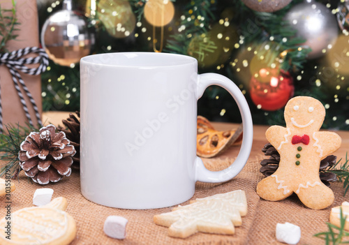 White ceramic coffee cup and christmas decoration on woon table background. mockup for creative advertising text message or promotional content.