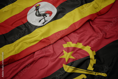 waving colorful flag of angola and national flag of uganda. Wallpaper Mural