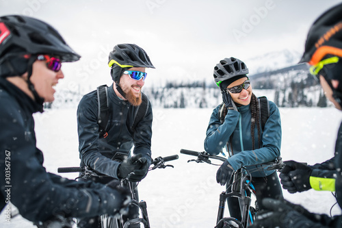 Group of mountain bikers standing on road outdoors in winter, talking.
