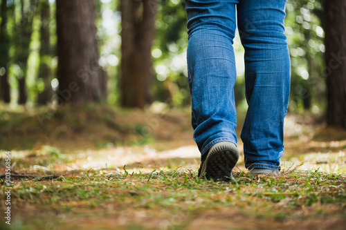 Foto  Close up legs walking to the pine forest