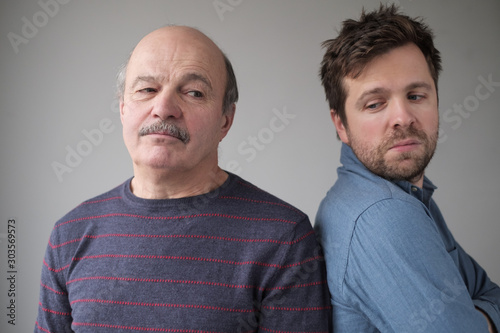 Mature caucasian man and son are offended on each other. Wallpaper Mural
