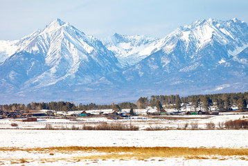 Siberia. Buryatia. View of the village of Nikolsk in the Tunka foothill valley against the backdrop of the majestic snowy mountains of the Eastern Sayan on a sunny winter day