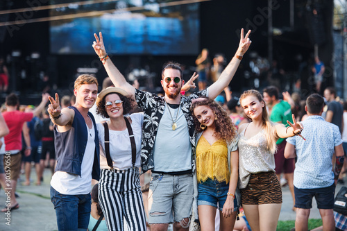 Group of young friends at summer festival. - 303570558